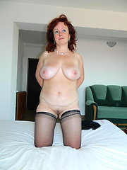 Sexy older woman lies in the bed and relaxing