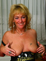 Blond mature woman in black leather boots rides pink vibrator