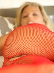 Amber Lynn Bach rolls around the bed in her sexy see thru crotchless bodystocking.
